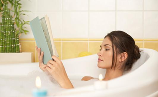 Frau liegt in der Badewanne und liest ein Buch