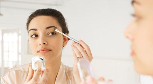 Eine Frau schminkt sich vor dem Spiegel