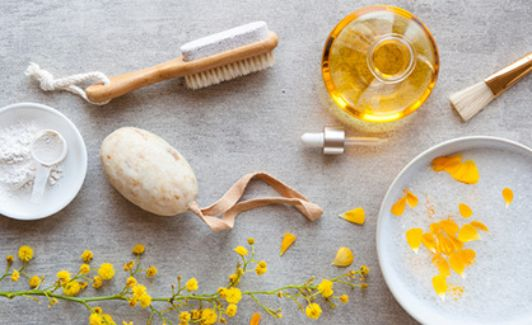 eine Schale Pulver, eine Naturseife, eine Bürste, ein Duftöl, ein Pinsel und ein Schale mit Blüten